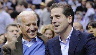 Then-Vice President Joe Biden, left, and his son Hunter Biden appear at the Duke Georgetown NCAA college basketball game in Washington on Jan. 30, 2010. (AP Photo/Nick Wass, File)