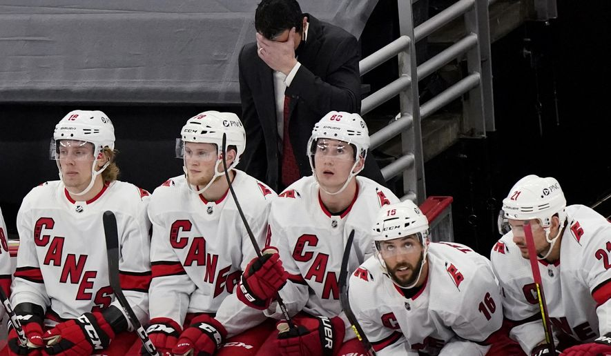 Carolina Hurricanes coach Rod Brind'Amour, top, reacts after Chicago Blackhawks' Alex DeBrincat scored a goal during the third period of an NHL hockey game in Chicago, Thursday, Feb. 4, 2021. (AP Photo/Nam Y. Huh)