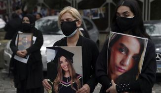 """Relatives of the victims of the Aug. 4, 2020 Beirut port explosion hold portraits of their loved ones who were killed, Thursday, Feb. 4, 2021 in Beirut, Lebanon.  The vigil at the seaport main entrance, marked six months since the blast that killed more than 200 people and injured thousands.  The Arabic words on poster read """"Who brought nitrates and for who? We have a right to know."""" (AP Photo/Bilal Hussein)"""