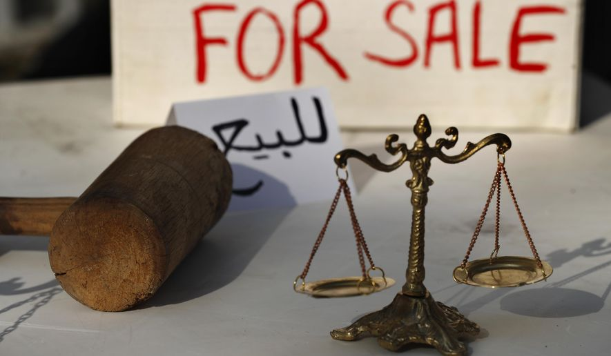 Lebanese activists display symbols of justice during a protest against the slow pace of the investigation into the August 4 explosion that hit Beirut's seaport, outside the Justice Palace, in Beirut, Lebanon, Dec. 3, 2020. The blast was one of the largest non-nuclear explosions in history and six months later, political and confessional rivalries have undermined the probe into the Beirut port explosion and brought it to a virtual halt, mirroring the same rivalries that have thwarted past attempts to investigate political crimes throughout Lebanon's history. (AP Photo/Hussein Malla)