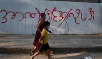 "Pedestrians pass by a graffiti reading as ""don't want dictatorship"" in Yangon, Myanmar, Tuesday, Feb. 4, 2021. Myanmar's new military government has blocked access to Facebook as resistance to Monday's coup surged amid calls for civil disobedience to protest the ousting of the elected civilian government and its leader Aung San Suu Kyi. (AP Photo)"