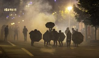 FILE - In this Sept. 18, 2020, file photo, tear gas fills the air during protests in Portland, Ore. An Oregon lawmaker is seeking to ban the use of tear gas and other agents against crowds of people in one of the most sweeping police measures in the country regarding crowd control devices. (AP Photo/Paula Bronstein, File)