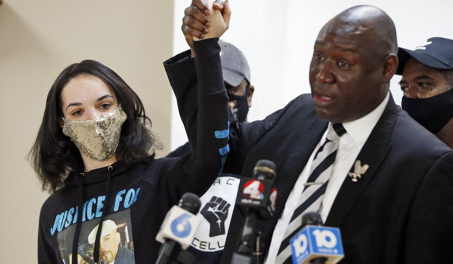 Ben Crump, right, the civil rights attorney representing Andre Hill's family, raises hands with Andre Hill's Daughter Karissa Hill during a news conference about the indictment of Columbus Police Officer Adam Coy in the shooting death of Andre Hill Thursday, Feb. 4, 2021, in Columbus, Ohio. Coy was indicted Wednesday on a murder charge by a Franklin County grand jury following an investigation by the Ohio Attorney General's office. (AP Photo/Jay LaPrete)
