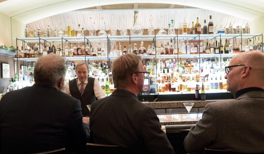 In this Tuesday, Nov. 27, 2018, file photo, a bartender talks to a customer at the Gotham Bar and Grill in New York. The Manhattan upscale restaurant hopes to reopen by summer 2021 if government regulations permit, but will likely have just 35 staffers instead of the 100 the restaurant had before it closed in March 2020. (AP Photo/Mary Altaffer)