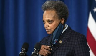 Chicago Mayor Lori Lightfoot removes her face mask before speaking during a press conference where she demanded the Chicago Teachers Union to reach a deal with Chicago Public Schools on a reopening plan at City Hall, Thursday morning, Feb. 4, 2021, in Chicago. (Pat Nabong/Chicago Sun-Times via AP)