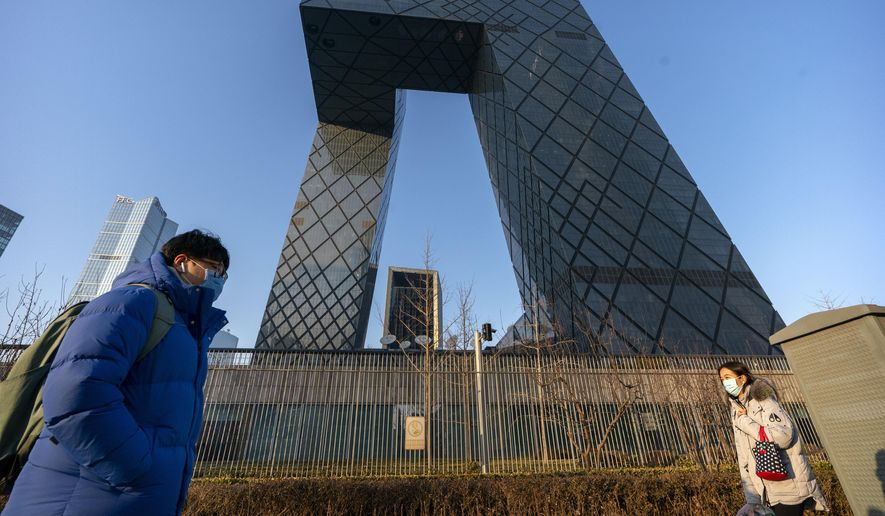 People wearing face masks to protect against the spread of the coronavirus walk past the CCTV Headquarters building, the home of Chinese state-run television network CCTV and its overseas arm CGTN, in Beijing, Thursday, Feb. 4, 2021. (AP Photo/Mark Schiefelbein)