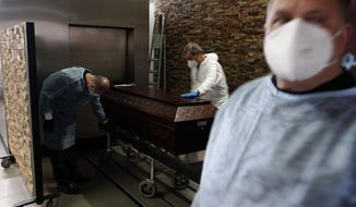 Funeral agency workers move the coffin of a COVID-19 victim to be cremated at a cemetery in Alcabideche, outside Lisbon, Wednesday, Feb. 3, 2021. Portugal is facing a pandemic surge that has made it the world's worst-hit country by size of population. (AP Photo/Armando Franca)