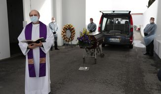 A priest says a few words during a brief ceremony outdoors before the cremation of a COVID-19 victim at a cemetery in Alcabideche, outside Lisbon, Wednesday, Feb. 3, 2021. Portugal is facing a pandemic surge that has made it the world's worst-hit country by size of population. (AP Photo/Armando Franca)
