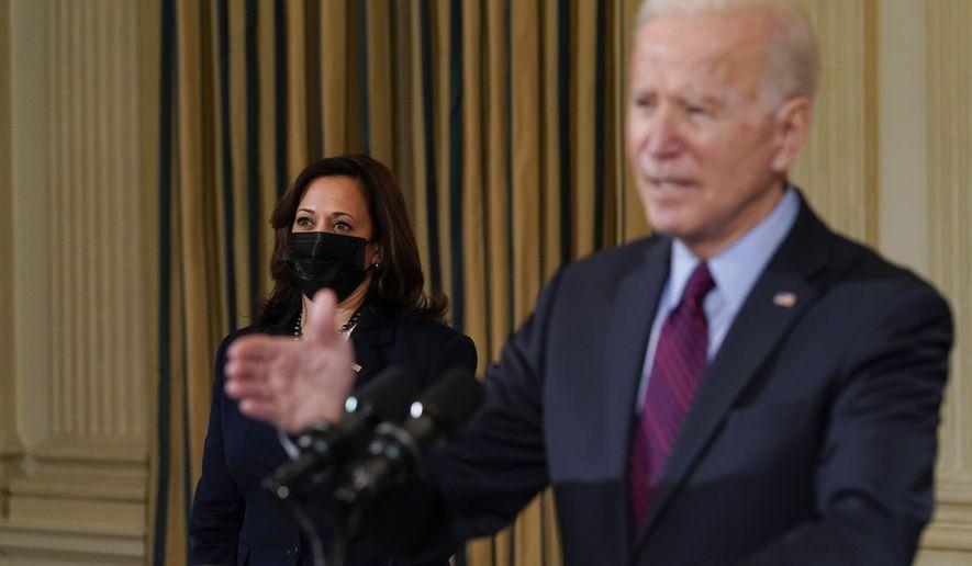 Vice President Kamala Harris listens as President Joe Biden speaks about the economy in the State Dinning Room of the White House, Friday, Feb. 5, 2021, in Washington. (AP Photo/Alex Brandon)