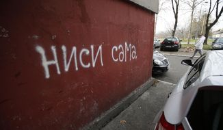"""In this photo taken Thursday, Jan. 28, 2021, a woman walks past a """"Nisi sama"""", which means """"You are not alone"""" slogan, in Belgrade, Serbia. A #MeToo-like movement is sweeping the strongly patriarchal Western Balkans and activists hope there will be no turning back. (AP Photo/Darko Vojinovic)"""