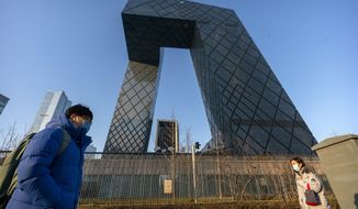 FILE- In this Thursday, Feb. 4, 2021 file photo, people wearing face masks to protect against the spread of the coronavirus, walk past the CCTV Headquarters building, the home of Chinese state-run television network CCTV and its overseas arm CGTN, in Beijing. The U.K. has stripped China's state-owned TV channel of its broadcasting license in the country, after an investigation found the license holder lacked editorial control and had links to China's ruling Communist Party. (AP Photo/Mark Schiefelbein, File)