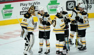 Boston Bruins' Tuukka Rask (40) and Anton Blidh (81) celebrate after an NHL hockey game against the Philadelphia Flyers, Friday, Feb. 5, 2021, in Philadelphia. (AP Photo/Matt Slocum)