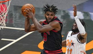Chicago Bulls forward Patrick Williams (9) grabs a rebound away from Orlando Magic forward James Ennis III (11) during the second half of an NBA basketball game Friday, Feb. 5, 2021, in Orlando, Fla. (AP Photo/John Raoux)
