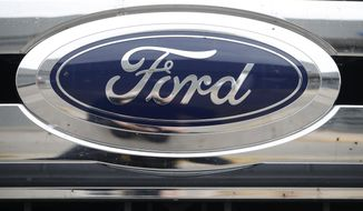 FILE - In this Oct. 20, 2019 file photograph, the company logo shines at a Ford dealership in Littleton, Colo.  The U.S. Justice Department and state of California have ended investigations into Ford Motor Co.'s gas mileage and emissions certification processes. Ford says in its annual report filed with the Securities and Exchange Commission on Friday, Feb. 5, 2021 that the DOJ and the California Air Resources Board told the company they don't intend to take further action.   (AP Photo/David Zalubowski, File)