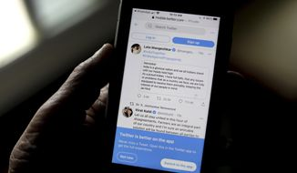 A person reads tweets by Indian celebrities, one of the many backing the Indian government, on his mobile in New Delhi, India, Thursday, Feb. 4, 2021. It took just one tweet from pop star Rihanna to anger the Indian government and supporters of Prime Minister Narendra Modi's party, after she tweeted about the farmer protests that have gripped India. Critics say the government has used the massive demonstrations to escalate a crackdown on free speech, detaining journalists and freezing Twitter accounts. Hundreds of Indian Twitter accounts, including those of news websites, activists and a farmers' union, were suspended on Monday. (AP Photo/Manish Swarup)