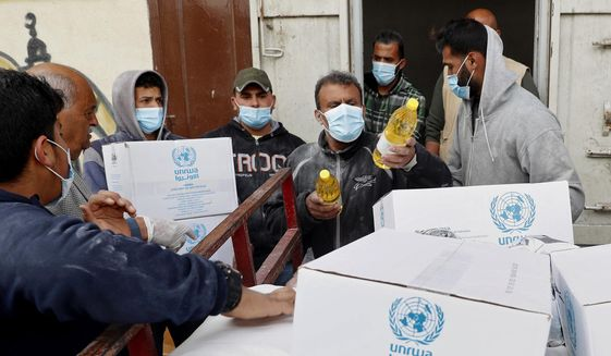 In this March 31, 2020 file photo, Palestinian workers load food supplies distributed by the United Nations Relief and Works Agency (UNRWA) at the Sheikh Redwan neighborhood of Gaza City.   (AP Photo/Adel Hana, File)  **FILE**