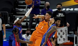 Phoenix Suns guard Devin Booker (1) passes over Detroit Pistons forward Jerami Grant, left, during the first half of an NBA basketball game, Friday, Feb. 5, 2021, in Phoenix. (AP Photo/Matt York)