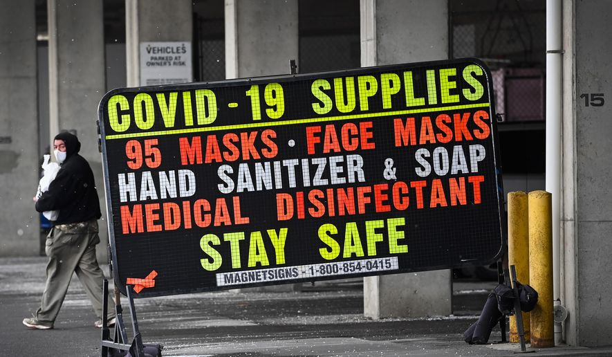 A man walks past a COVID-19 retail supplies sign during the COVID-19 pandemic in Toronto, Friday, Feb. 5, 2021. (Nathan Denette/The Canadian Press via AP)