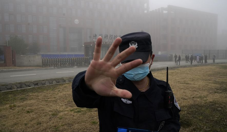 In this Feb. 3, 2021, file photo, a security person moves journalists away from the Wuhan Institute of Virology after a World Health Organization team arrived for a field visit in Wuhan in China's Hubei province. A member of the expert team investigating the origins of the coronavirus in Wuhan says the Chinese side granted full access to all sites and personnel they requested to visit and meet with. (AP Photo/Ng Han Guan, File)  **FILE**