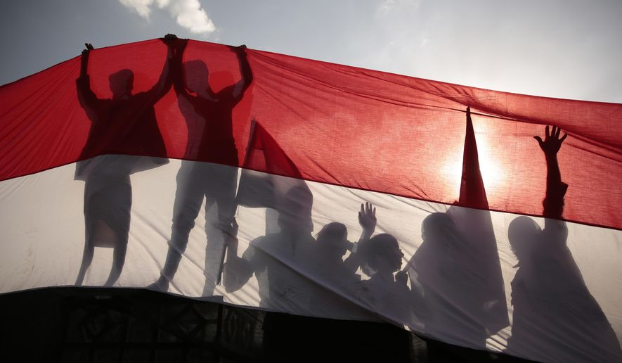 FILE - In this Sept. 26, 2016, file photo, men are silhouetted against a large representation of the Yemeni flag as they attend a ceremony to mark the anniversary of North Yemen's Sept. 26, 1962 revolution in Sanaa, Yemen. President Joe Biden's announcement that the U.S. will end its support of a Saudi-led coalition's years-long war against Yemen's Houthi rebels likely will increase pressure on the kingdom to end its campaign there, though reaching an enduring peace for the Arab world's poorest country still remains in question. (AP Photo/Hani Mohammed, File)