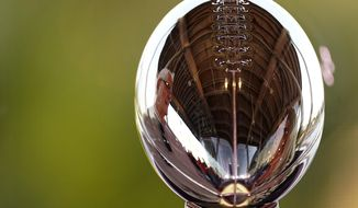 A man is reflected in the Lombardi Trophy at the NFL Experience Thursday, Feb. 4, 2021, in Tampa, Fla. The city is hosting Sunday's Super Bowl football game between the Tampa Bay Buccaneers and the Kansas City Chiefs. (AP Photo/Charlie Riedel) **FILE**
