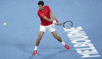 Serbia's Novak Djokovic makes a backhand return to Germany's Alexander Zverev during their ATP Cup match in Melbourne, Australia, Friday, Feb. 5, 2021.(AP Photo/Hamish Blair)