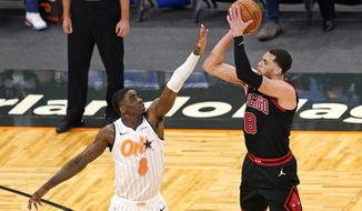 Chicago Bulls guard Zach LaVine, right, makes a 3-point shot over Orlando Magic forward Dwayne Bacon, left, during the first half of an NBA basketball game, Saturday, Feb. 6, 2021, in Orlando, Fla. (AP Photo/John Raoux)