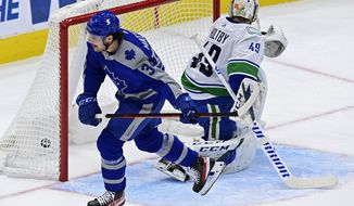 Toronto Maple Leafs center Auston Matthews (34) scores against Vancouver Canucks goaltender Braden Holtby (49) during first-period NHL hockey game action in Toronto, Saturday, Feb. 6, 2021. (Frank Gunn/The Canadian Press via AP)