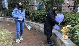 """Residents visiting the Wuhan Central Hospital offer flowers in memory of Li Wenliang, the whistleblower doctor who sounded the alarm and was reprimanded by local police for it in the early days of Wuhan's pandemic, prior to the anniversary of his death, in central China's Hubei province, Saturday, Feb. 6, 2021.  Dr. Li Wenliang died in the early hours of Feb. 7 from the virus first detected in this Chinese city. A small stream of people marked the anniversary at the hospital. The 34-year-old became a beloved figure and a potent symbol in China after it was revealed that he was one the whistleblowers who authorities had punished early for """"spreading rumors"""" about a SARS-like virus. (AP Photo/Ng Han Guan)"""
