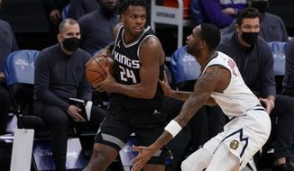 Sacramento Kings guard Buddy Hield, left, looks to pass against Denver Nuggets forward Will Barton, right, during the first half of an NBA basketball game in Sacramento, Calif., Saturday, Feb. 6, 2021. (AP Photo/Rich Pedroncelli)