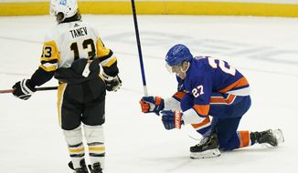 New York Islanders' Anders Lee (27) celebrates after scoring a goal as Pittsburgh Penguins' Brandon Tanev (13) skates away during the third period of an NHL hockey game Saturday, Feb. 6, 2021, in Uniondale, N.Y.  (AP Photo/Frank Franklin II)