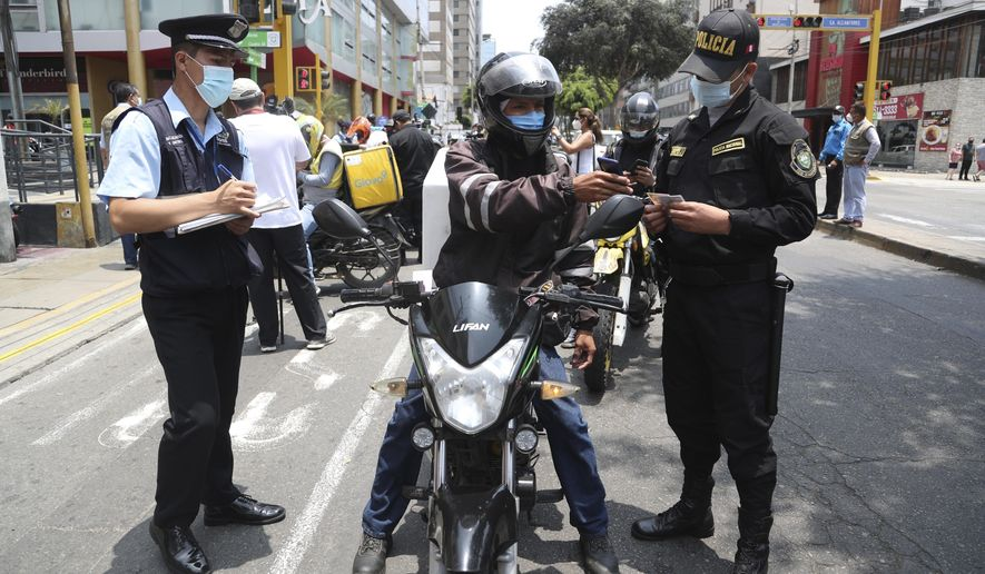 A Venezuelan migrant shows his documents during a security check in the Miraflores district of Lima, Peru, Sunday,  Jan. 24, 2021. Peru is hosting roughly 1 million displaced Venezuelans, an influx that began around 2014 as inflation, unemployment, crime and shortages of food and medicine soared in their homeland. (AP Photo/Martin Mejia)