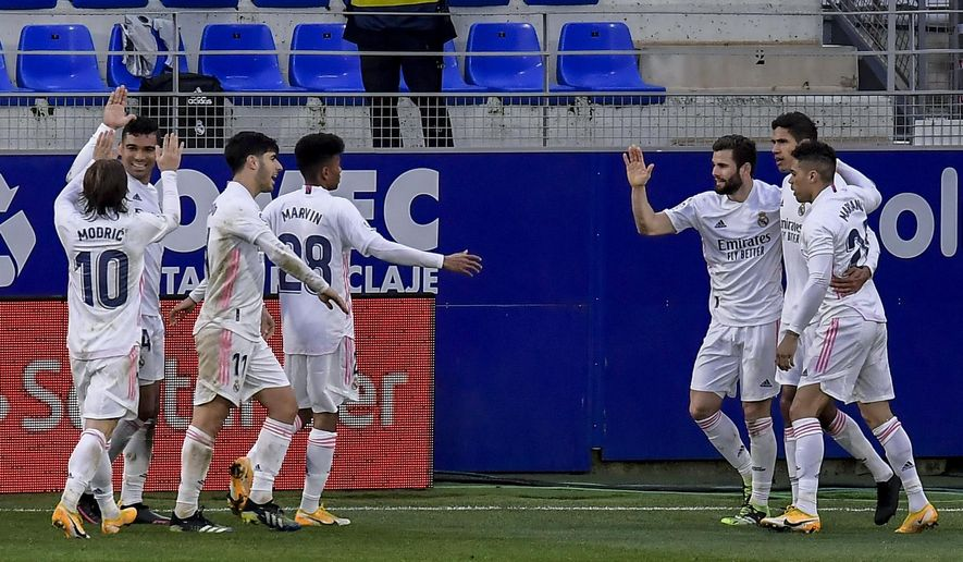 Real Madrid's Raphael Varane, second right, celebrates after scoring his side's second goal during the Spanish La Liga soccer match between Huesca and Real Madrid at El Alcoraz stadium in Huesca, Spain, Saturday, Feb. 6, 2021. (AP Photo/Alvaro Barrientos)