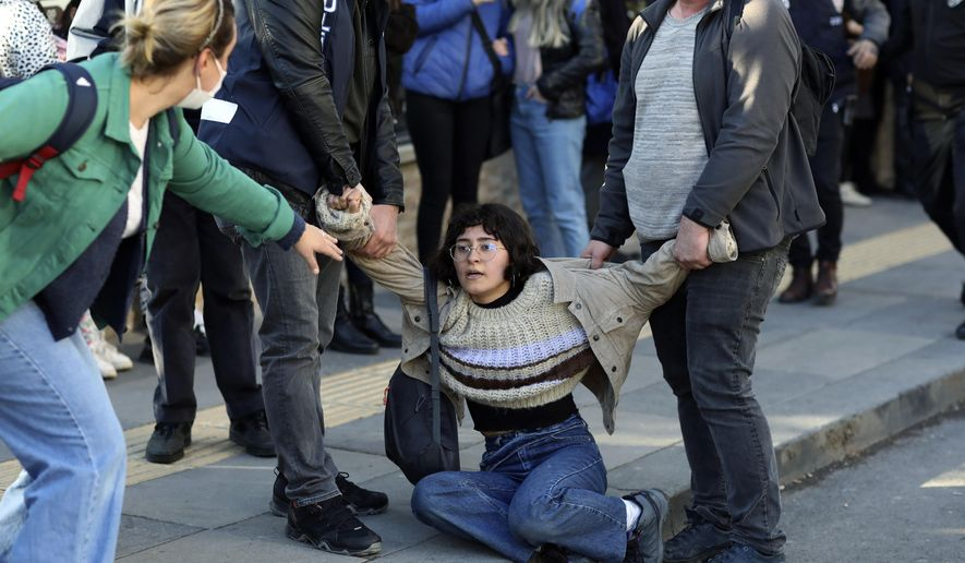 A woman reacts as riot police officers detain a student during a protest, in Ankara, Turkey, Friday, Feb. 5, 2021. Students and faculty members at Bogazici University have been staging demonstrations in protest of President Recep Tayyip Erdogan's Jan. 1 appointment of an academic with links to his ruling party, as rector.(AP Photo/Burhan Ozbilici)