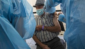 Alejandro Pavez, 91, receives a dose of China's Sinovac Biotech COVID-19 vaccine at a vaccination center set up at the Bicentenario Stadium in Santiago, Chile, Wednesday, Feb. 3, 2021. Chile is starting its vaccination plan for the general population on Wednesday with seniors over 90 and health workers. (AP Photo/Esteban Felix)