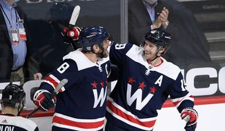 Washington Capitals center Nicklas Backstrom (19), of Sweden, celebrates his goal with left wing Alex Ovechkin (8), of Russia, during the second period of an NHL hockey game against the Philadelphia Flyers, Sunday, Feb. 7, 2021, in Washington. (AP Photo/Nick Wass)