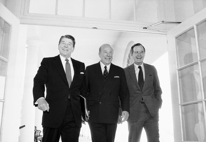 Secretary of State George Shultz, center, walks with President Ronald Reagan and Vice President George Bush upon his arrival at the White House in Washington, after two days of arms talks with the Soviet Union in Geneva. Shultz, former President Reagan's longtime secretary of state, who spent most of the 1980s trying to improve relations with the Soviet Union and forging a course for peace in the Middle East, died Saturday, Feb. 6, 2021. He was 100. (AP Photo/Barry Thumma, File)
