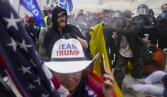 In this Jan. 6, 2021, file photo rioters loyal to President Donald Trump try to break through a police barrier at the Capitol in Washington. Arguments begin Tuesday, Feb. 9, in the impeachment trial of Donald Trump on allegations that he incited the violent mob that stormed the U.S. Capitol on Jan. 6. (AP Photo/John Minchillo, File)