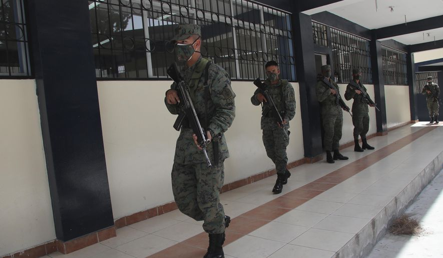 Soldiers guard a polling place a day ahead of the general elections, in Quito, Ecuador, Saturday, Feb. 6, 2021. Ecuador is heading towards general elections Sunday in which 16 candidates are vying for president amid a fragmented political landscape marred by economic turmoil and the bleak impacts of the new coronavirus pandemic. (AP Photo/Dolores Ochoa)