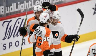 Philadelphia Flyers left wing Scott Laughton (21) celebrates his second goal with left wings Joel Farabee (86) and James van Riemsdyk (25) during the second period of an NHL hockey game against the Washington Capitals, Sunday, Feb. 7, 2021, in Washington. (AP Photo/Nick Wass)