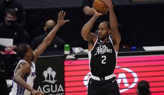 Los Angeles Clippers forward Kawhi Leonard, right, shoots as Sacramento Kings forward Harrison Barnes defends during the first half of an NBA basketball game Sunday, Feb. 7, 2021, in Los Angeles. (AP Photo/Mark J. Terrill)