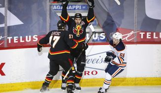 Edmonton Oilers' Kailer Yamamoto, right, skates past as Calgary Flames' Mikael Backlund, center, celebrates his goal with Milan Lucic during the second period of an NHL hockey game Saturday, Feb. 6, 2021, in Calgary, Alberta. (Jeff McIntosh/The Canadian Press via AP)