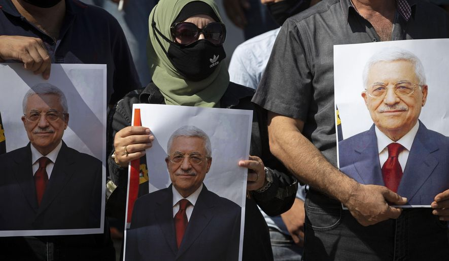In this Sept. 27, 2020, file photo, Palestinians wearing protective face masks amid the coronavirus pandemic, hold pictures of Palestinian President Mahmoud Abbas during a rally to support Abbas, in the West Bank town of Tubas. President Abbas called for legislative elections on May 22 and presidential elections on July 31, 2021. (AP Photo/Majdi Mohammed, File)