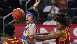 UCLA's Jaime Jaquez Jr., back left, and Southern California guard Isaiah White, right, go after a rebound as Southern California forward Chevez Goodwin watches during the first half of an NCAA college basketball game Saturday, Feb. 6, 2021, in Los Angeles. (AP Photo/Mark J. Terrill)