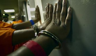 Handcuffed inmates line up against the wall in a corridor outside their cells at the Washington, D.C. Central Detention facility (The Washington Times)