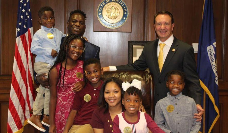 Louisiana Attorney General Jeff Landry poses with Nyron Harrison and his family. )Photo courtesy Louisiana attorney general's office.)