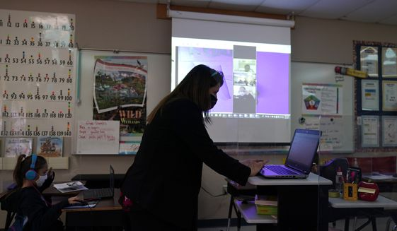 Wylona Rogers teaches students attending a class in-person as well as students attending virtually at Driggers Elementary School, Monday, Feb. 8, 2021, in San Antonio. After seeing two academic years thrown off course by the pandemic, school leaders around the country are planning for the possibility of more distance learning next fall at the start of yet another school year. (AP Photo/Eric Gay) **FILE**