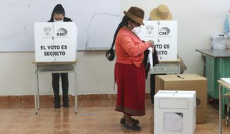 A woman votes during general elections in Cangahua, Ecuador, Sunday, Feb. 7, 2021. Amidst the new coronavirus pandemic Ecuadoreans went to the polls in a first round presidential and legislative election. (AP Photo/Dolores Ochoa)