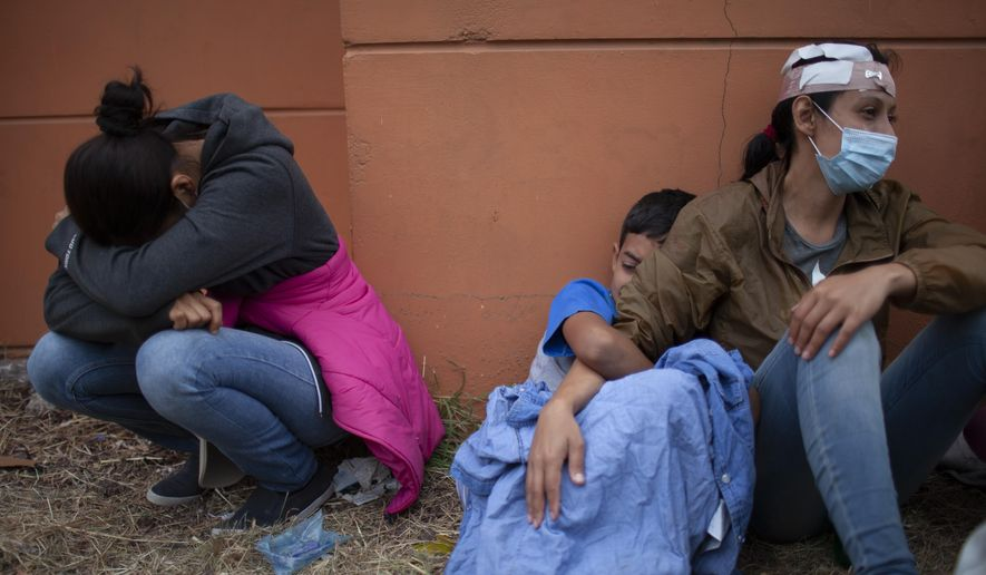 In this Jan. 17, 2021, photo, injured women, part of a Honduran migrant caravan in their bid to reach the U.S. border, weep as they sit on the side of a highway after clashing with Guatemalan police and soldiers in Vado Hondo, Guatemala, Guatemala. U.S. Federal law allows immigrants facing credible threats of persecution or violence in their home country to seek U.S. asylum. (AP Photo/Sandra Sebastian) **FILE**