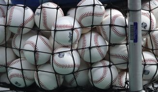 FILE - In this July 3, 2020, file photo, balls marked with Cactus League spring training logos are in a basket during Kansas City Royals baseball practice at Kauffman Stadium in Kansas City, Mo. Major League Baseball has slightly deadened its baseballs amid a years-long surge in home runs.MLB anticipates the changes will be subtle, and a memo to teams last week cites an independent lab that found the new balls will fly 1 to 2 feet shorter on balls hit over 375 feet. (AP Photo/Charlie Riedel, File)